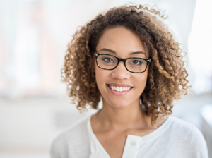 Black happy female wearing glasses with a big smile against a white background